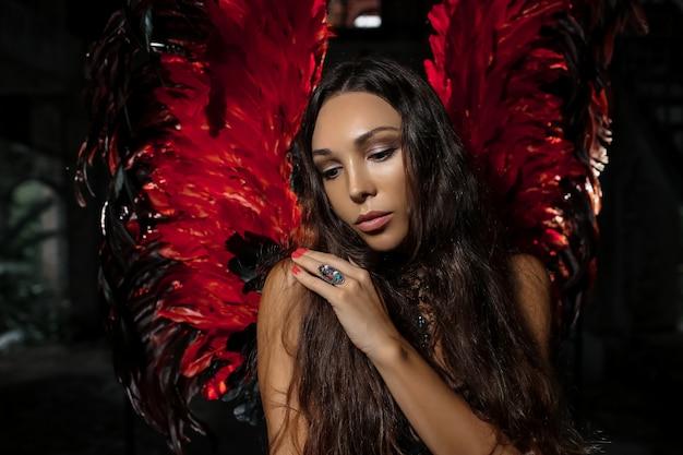 赤い暗い天使の羽でポーズをとって繊細な美しいブルネットの女性の肖像画を閉じます。スタジオ撮影。