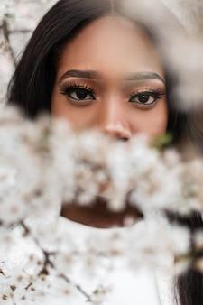 꽃 근처의 카메라를 놀라운 표정으로 바라보는 유쾌한 젊은 흑인 여성의 클로즈업 초상화. 표현 표정으로 예쁜 여자는 카메라를 찾습니다. 뷰티 라이프 스타일