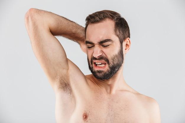 Крупным планом портрет бородатого мужчины с отвращением, стоящего изолированно над белой и нюхающего его подмышку