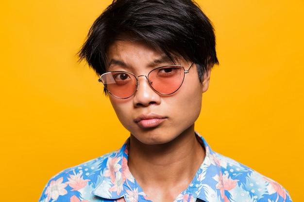 サングラスで疑わしいアジア人男性の肖像画をクローズアップ