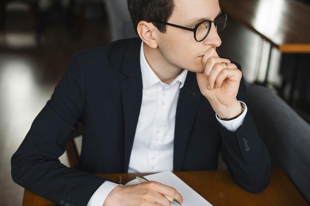 노트북에서 짜는 동안 심각 하 게 손으로 그의 입술을 만지고 그의 노트북을보고 우아한 성인 관리자의 초상화를 닫습니다.