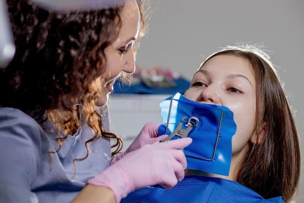 Крупным планом портрет пациентки, посещающей стоматолога для отбеливания зубов в клинике.
