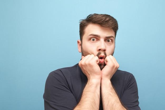 Макро портрет испуганного мужчины с бородой на синем