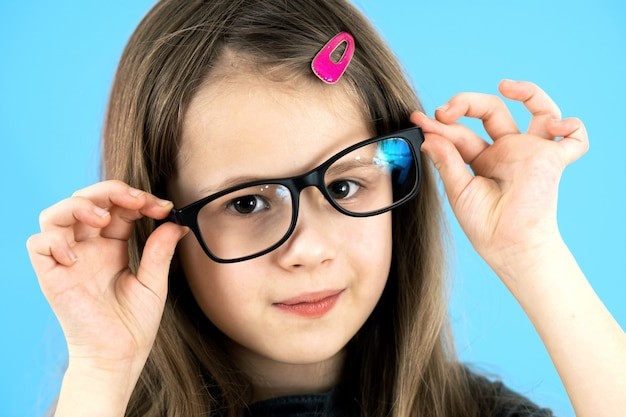 Крупным планом портрет смешные ребенка школьница носить очки, изолированных на синей стене
