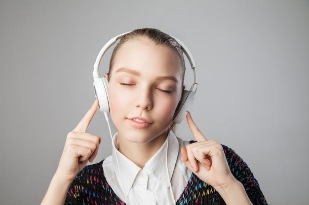 目を閉じて、灰色の背景に分離された笑顔でヘッドフォンで女の子の肖像画を閉じます。