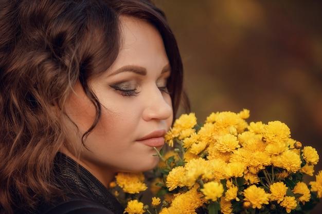 그녀의 얼굴 근처에 꽃의 꽃다발을 가진 여자의 클로즈업 초상화