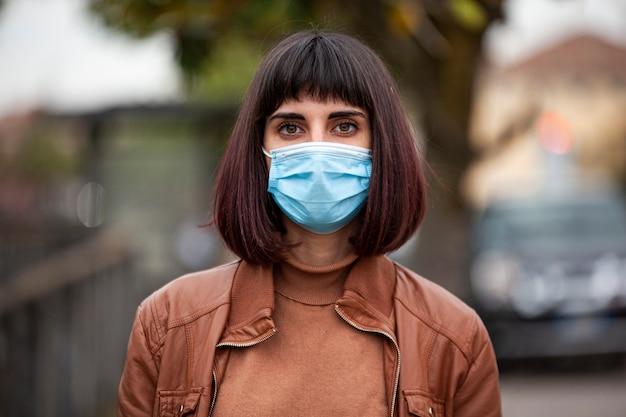 Крупным планом портрет девушки с медицинской маской на открытом воздухе во время карантина covid в италии