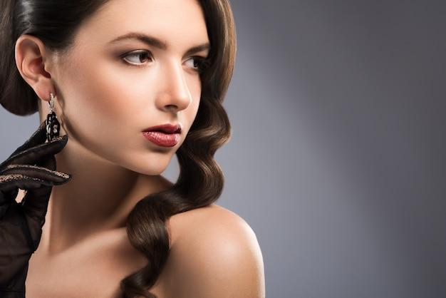우아하게 멀리보고 붉은 입술으로 화려한 갈색 머리 여자의 초상화를 닫습니다