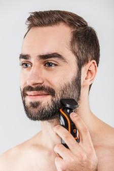 Крупным планом портрет красивого бородатого мужчины, бреющегося электрической бритвой, изолированного на белом