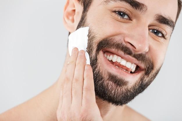 Крупным планом портрет красивого бородатого мужчины, стоящего изолированно над белой, применяя пену для бритья