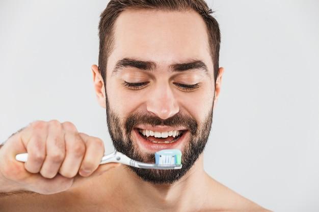 Крупным планом портрет красивого бородатого мужчины, стоящего изолированно над белой и чистящего зубы