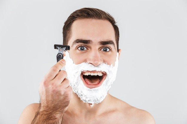 Крупным планом портрет красивого бородатого мужчины с пеной для бритья на лице, стоящего изолированно над белой, готового к бритью