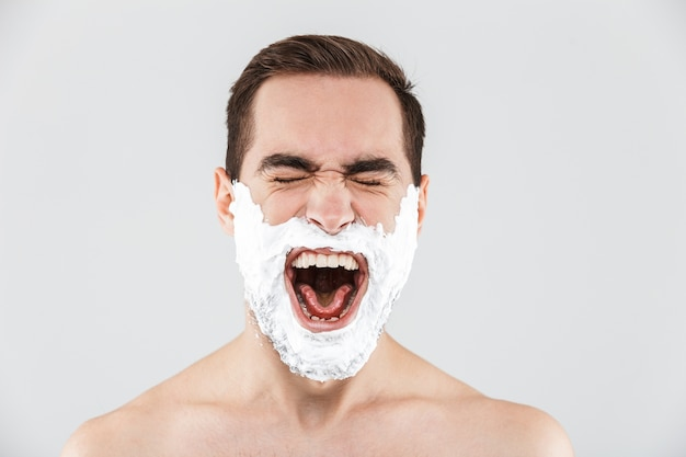 Крупным планом портрет красивого бородатого мужчины с пеной для бритья на лице, изолированном над белой