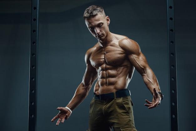 Закройте вверх по портрету красивого человека фитнеса в белой рубашке в спортзале.