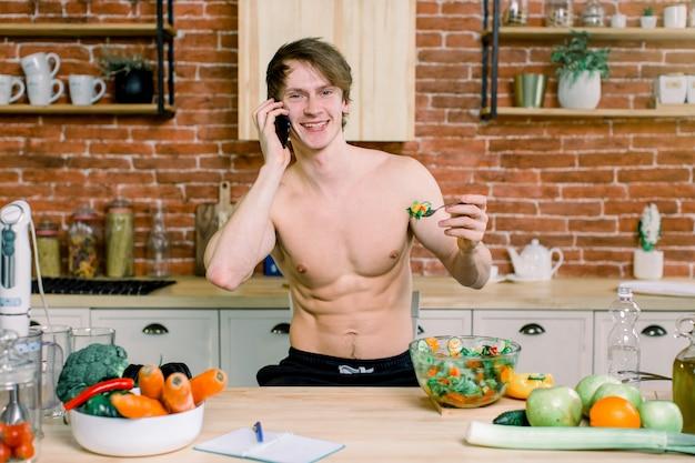 新鮮な野菜のサラダを食べて、赤レンガの壁のキッチンの背景にスマートフォンを使用してハンサムな男のクローズアップの肖像画。健康とビーガンフードのコンセプト