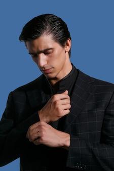 青い暗い背景の上の黒いスーツを着たハンサムな深刻な若い男の肖像画をクローズアップ。垂直方向のビュー。