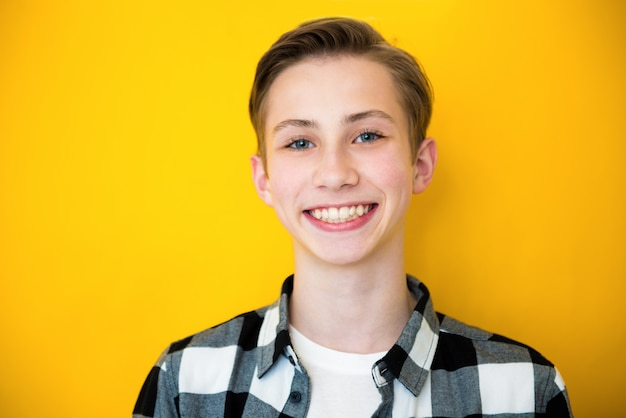 黄色の背景の上に、ハンサムな十代の少年の肖像画をクローズアップ