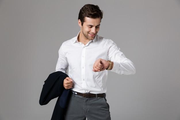 Крупным планом портрет красивого молодого бизнесмена, стоящего изолированно над серой стеной и держащего куртку, проверяя время