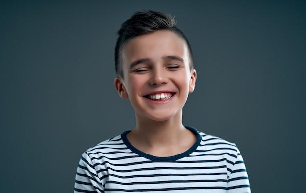 회색에 웃 고 행복 한 소년의 초상화를 닫습니다.
