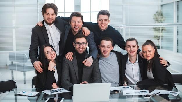 閉じる。職場で幸せなビジネスチームの肖像画。チームワークの概念