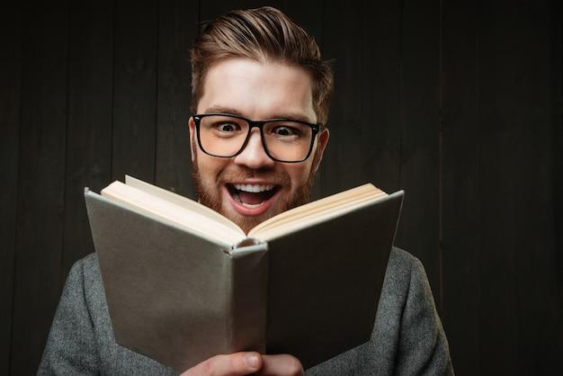 Крупным планом портрет счастливого веселого человека в очках, читая книгу, изолированную на черном деревянном фоне Premium Фотографии