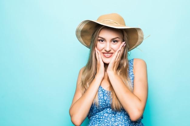 파란색 배경 위에 절연 카메라를 찾고 입으로 해변 모자에 행복 흥분된 젊은 여자의 초상화를 닫습니다