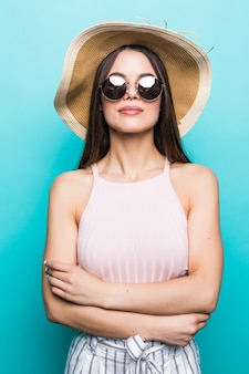 青い壁に隔離されたカメラを見て口を開けてビーチ帽子で幸せな興奮した若い女性の肖像画を閉じます。