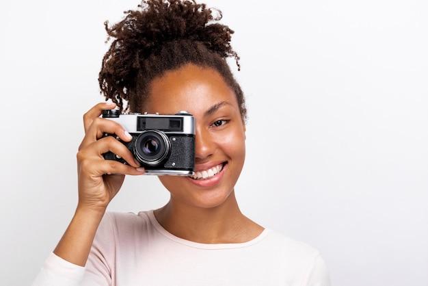 彼女の手でそれを探している写真カメラで幸せなムラート旅行者の女の子の肖像画を間近します。