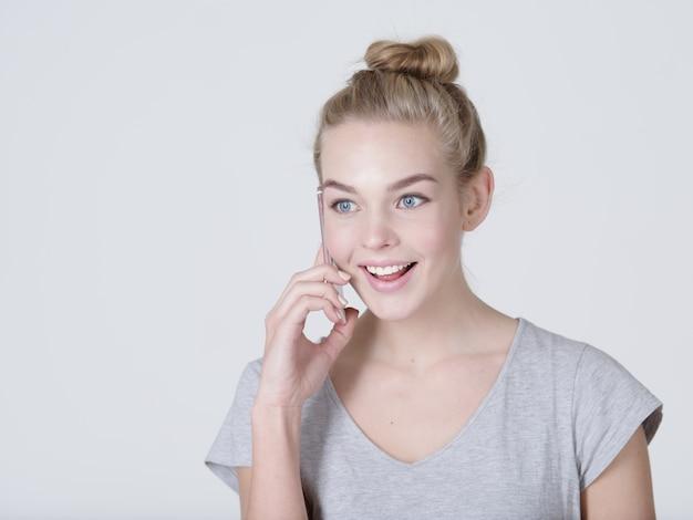 Крупным планом портрет счастливой женщины, говорящей по мобильному телефону на сером bacjground