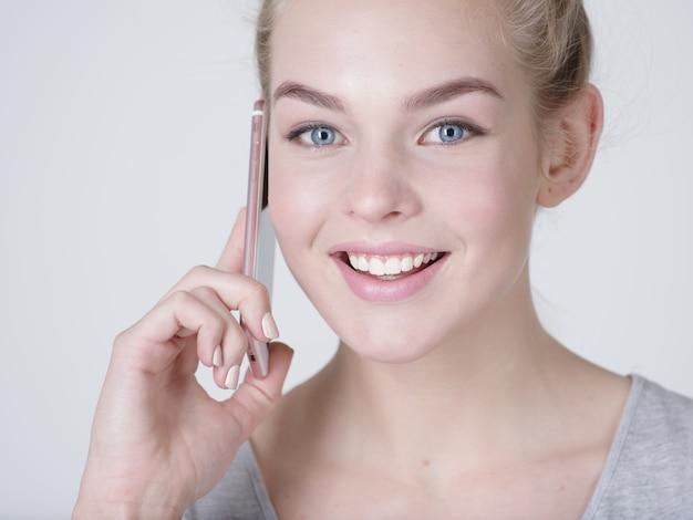 회색 bacjground에 휴대 전화로 이야기하는 행복한 여자의 초상화를 닫습니다