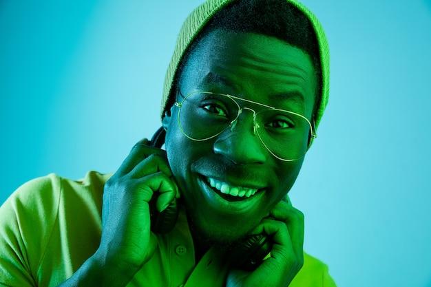 黒のネオンスタジオの背景に笑みを浮かべて幸せな若いアフリカ系アメリカ人男性の肖像画をクローズアップ