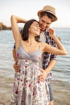 Крупным планом портрет счастливой молодой пары в любви, стоя на пляже и обниматься