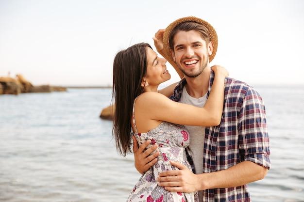Крупным планом портрет счастливой молодой хипстерской влюбленной пары, стоящей на пляже и обнимающейся