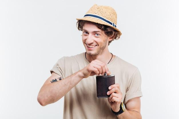 흰색 배경에 고립 된 알코올 플라스크를 들고 행복 한 젊은 남자의 클로즈 업 초상화