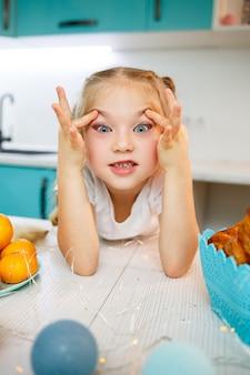 일곱 살 어린 소녀의 초상화를 닫습니다. 부엌에서 테이블에 앉아 장난. 흰색 티셔츠를 입고