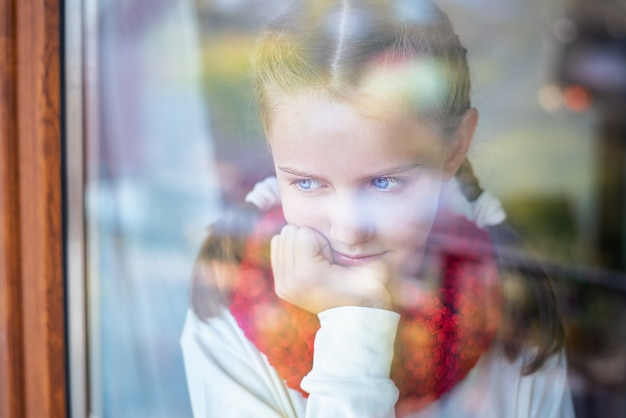 Крупным планом портрет маленькой девочки, которая смотрит в окно.