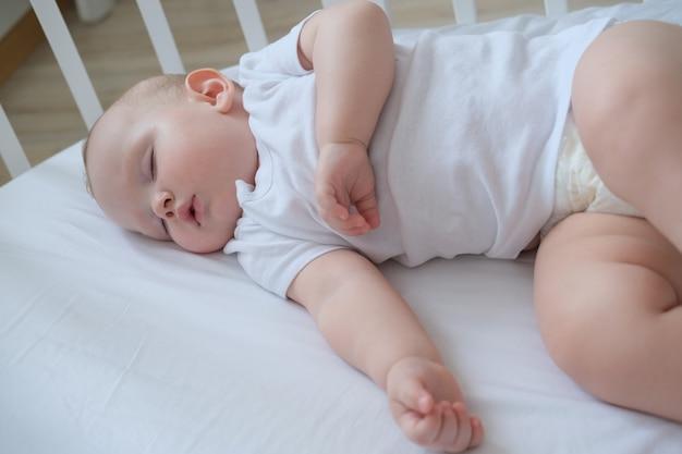 Макро портрет маленького спящего ребенка в кроватке.
