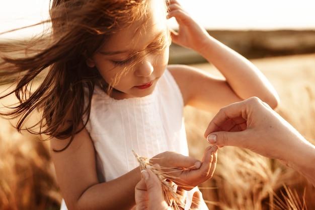 風が日没に対して彼女の髪で遊んでいる間、小麦を手に持っている白いドレスを着た素敵な少女の肖像画を閉じます。
