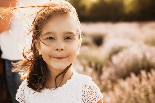밖에 서 웃 고 사랑스러운 어린 소녀의 초상화를 닫습니다. 바람이 그녀의 머리를 불고있는 동안 일몰에 대해 웃고있는 카메라를보고있는 아이.