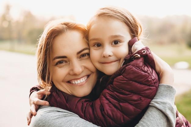 公園の屋外の夕日に対して笑っているカメラを見ている娘を抱きしめる素敵な母親の肖像画を閉じます。