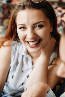 カフェに座っている手で彼女の首を保持しながら笑っているカメラを見ている赤い髪の素敵なプラスサイズの女性の肖像画を閉じます。