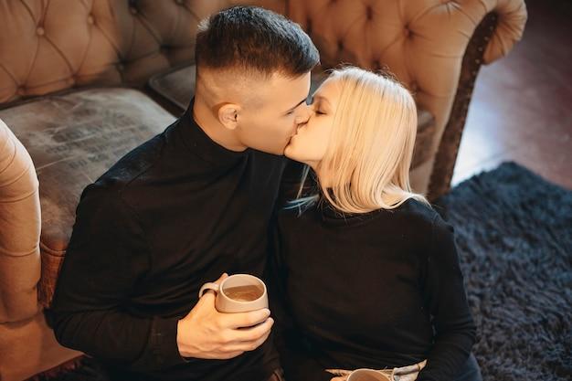 ソファでホットコーヒーリーニンを飲みながら、自宅の床でキスしている素敵な若いカップルの肖像画を閉じます。