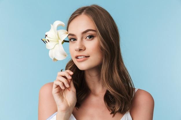 Крупным планом портрет прекрасной молодой девушки с цветком лилии