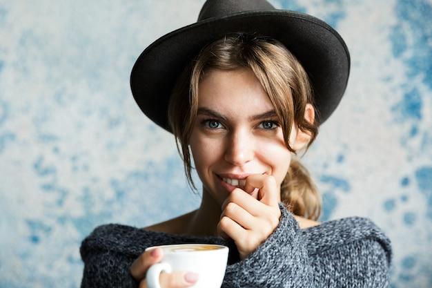 뜨거운 커피 한잔 들고 파란색 벽에 스웨터와 모자를 입고 사랑스러운 젊은 여자의 초상화를 닫습니다