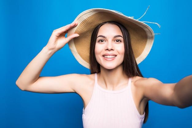青い壁に隔離されたselfieを取っている夏のドレスと麦わら帽子の素敵な若い女性の肖像画を閉じます。