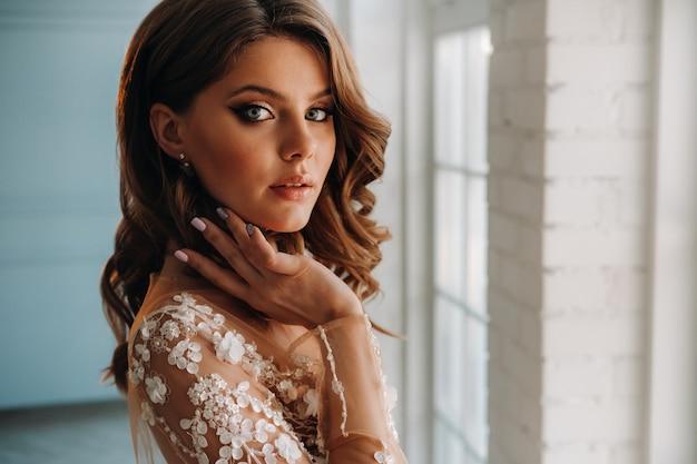 彼女のインテリアで朝のウェディングドレスを着た豪華な花嫁のクローズアップの肖像画。