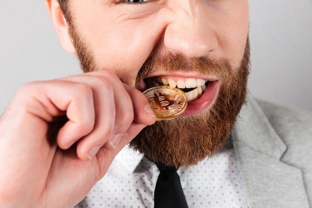 Крупным планом портрет человека, кусающего золотой биткойн