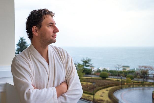 海を見下ろすホテルのバルコニーに立っている白いバスローブを着た男のクローズアップの肖像画