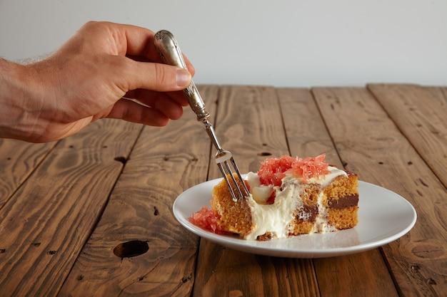 Крупным планом портрет мужской руки с серебряной вилкой, берущей кусок светло-коричневого бисквитного торта с белой тарелки