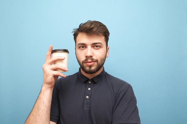 彼の手でコーヒーの紙コップで青にひげ立っている男のクローズアップの肖像画